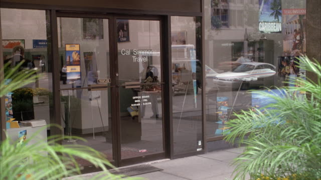 MEDIUM ANGLE ESTABLISHING SHOT OF GLASS DOORS TO 'CAL SIMMON TRAVEL' AGENCY. STOREFRONT IS ALL GLASS, SEE REFLECTION OF PEDESTRIANS AND OTHER BUILDINGS IN GLASS. FERNS OR BUSHES VISIBLE IN FOREGROUND.