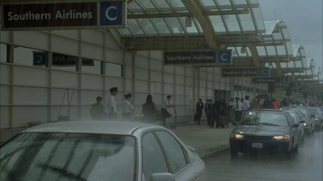 vidéos et rushes de medium angle of entrance or drop-off curb at ronald reagan washington national airport in rain. see people walking on left under awning. see people waiting in cars on street. see taxi pull up to curb and rear passenger door open. - aéroport ronald reagan