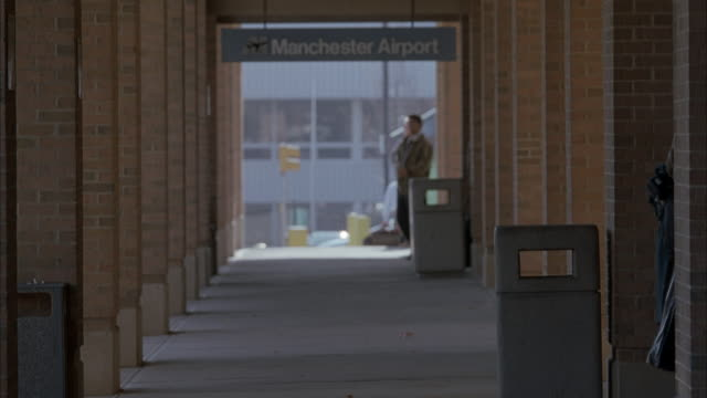 """medium angle of covered outdoor walkway or hallway at airport. see sign overhead reading """"manchester airport."""" see travelers or pedestrians enter from sides walking down hallway. see man in trench coat running away from pov. see brick columns lining walkw - 1997 stock videos and b-roll footage"""