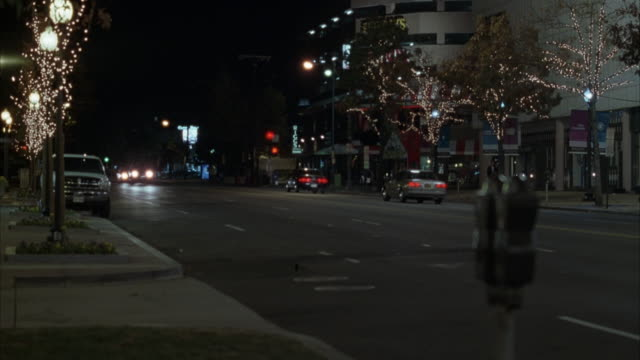 medium angle of town street with christmas decorations. cars drive on street, suv with flashing police siren light drives from back towards frame. - blaulicht stock-videos und b-roll-filmmaterial
