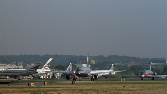 medium angle of two commercial airliners waiting to taxi on tarmac of ronald reagan national airport. see several other commercial airliners, airplane, plane or jet parked at terminal gates in left background. see grass area in foreground. see low hill wi - flughafen washington ronald reagan national stock-videos und b-roll-filmmaterial