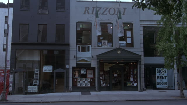 "medium angle of storefronts on city street in probably a small town. stores are two or three stories high. store on right has ""rizzoli"" written on front. see two white and green flags hanging from store as well. it is not clear what the stores are selling - anno 1994 video stock e b–roll"