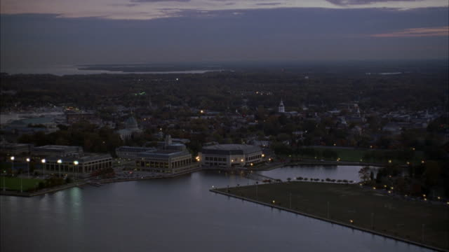 aerial of waterfront area with government buildings, pov moves down to black lincoln towncar on bridge moving to right. - long island video stock e b–roll