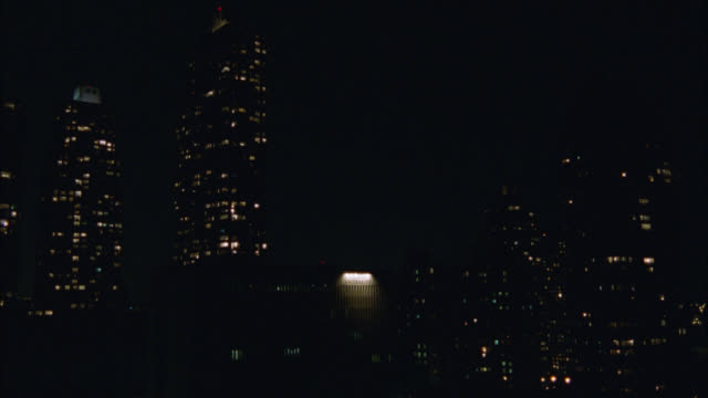 WIDE ANGLE OF CITY SKYLINE AT NIGHT. SEE LIGHT COMING FROM TALL MULTI-STORY BUILDINGS. COULD BE HIGH RISES, HOTELS, OR OFFICE BUILDINGS. SEE LARGE BUILDING WITH ONE LARGE, BRIGHT LIGHT IN CENTER. SHOT GOES OUT OF FOCUS. NEW YORK.