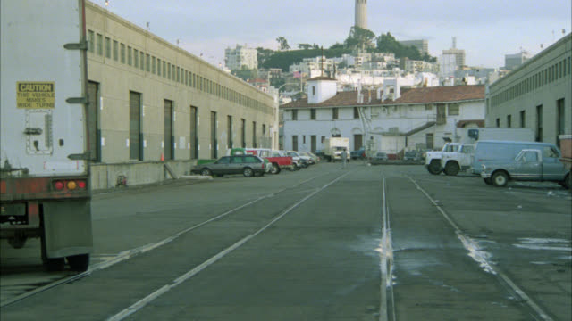 wide angle est warehouse area in san francisco harbor area.  large white truck to and by camera. coit tower in far bg.  note: cable car tracks or rails on ground. landmark. - north beach san francisco stock videos & royalty-free footage