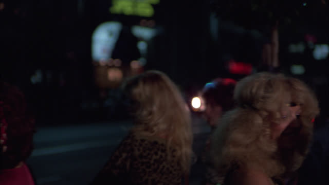 medium angle of prostitutes and pedestrians on sidewalk of hollywood boulevard. camera pans right to left as police car drives by with flashing lights or bizbar. city street. - 売春者点の映像素材/bロール