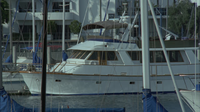wide angle of a large or boat moored in slip marina. sailboats, masts in fg. docks. - marina stock videos & royalty-free footage