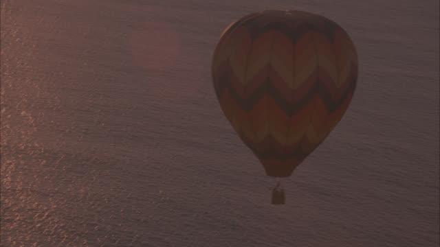 vídeos de stock e filmes b-roll de aerial circling around multi-colored  hot air balloon over calm water, ocean. people in the basket. - ilhas do pacífico