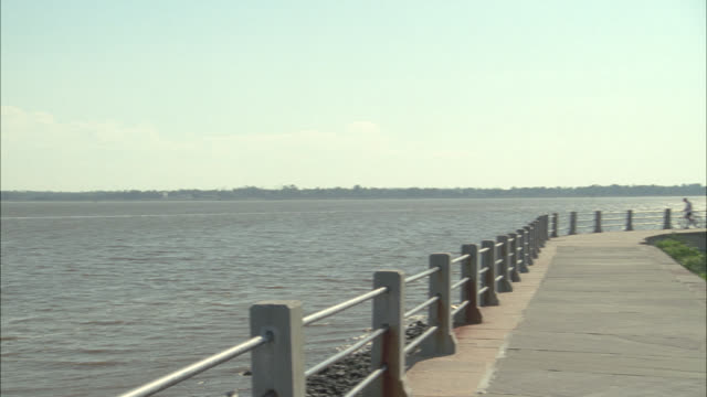 PAN LEFT TO RIGHT FROM WATER, LAKE PONTCHARTRAIN, AND BIKE PATH OR WALKING TO PARK WITH MONUMENT IN CENTER.