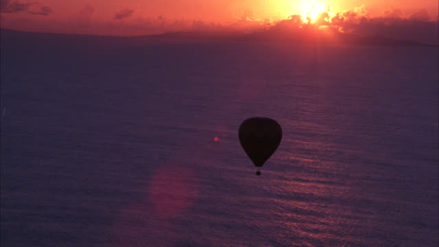vidéos et rushes de aerial of multi-colored hot air balloon floating over ocean at sunset. sun on horizon. - polynésie française