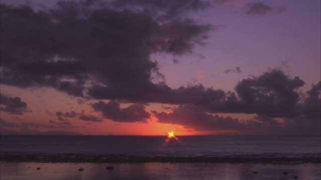 wide angle of beach or shore at sunset. waves crash onto beach. clouds. could be sunrise. - 太平洋点の映像素材/bロール