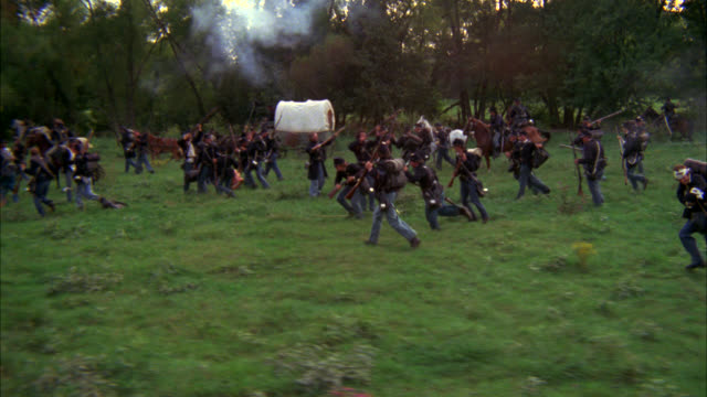 stockvideo's en b-roll-footage met pull back from medium angle of civil ware union soldiers on horseback riding through field. could be battle or retreat. men shoot rifles. trees surround field. camera pulls back to high angle down of retreat. covered wagons. battlefields. - burgeroorlog