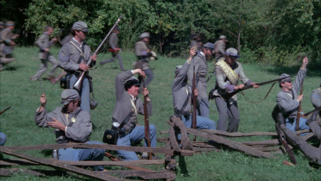 medium angle of confederate civil war soldiers with rifles shooting across field. gunfire. men fall to ground. wounded. camera pans right to left from men with rifles to cannon in bg. could be battlefield. stunts. - confederate states of america stock videos & royalty-free footage