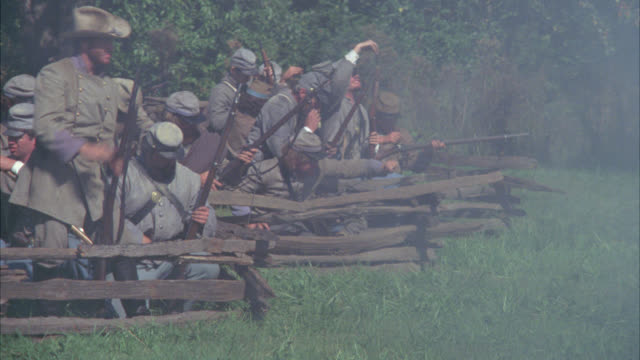 medium angle of confederate civil war soldiers with rifles shooting across field. gunfire. men fall to ground. wounded. could be battlefield. stunts. - confederate states of america stock videos & royalty-free footage