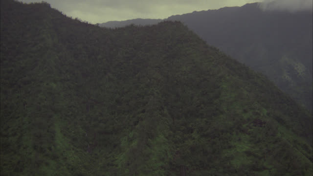 vidéos et rushes de aerial of mountains with tropical rainforest or jungle. waterfalls over cliffs. could be island, southeast asia or hawaii. matching r940-4 r940-5. - angle de prise de vue