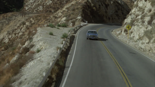 process plate straight back of blue sedan car driving on desert highway or road. could be winding mountain road. dry, arid landscape. could be valley or canyon. cliffs and brush on side of road. car pulls off road. telephone poles and wires visible. - ledge stock videos & royalty-free footage