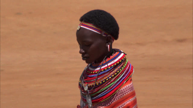 pan right to left of a native masai woman wearing colorful jewelry and robe walking down dirt path past camera. matching shots of masai in village wearing native tribal attire robes dresses jewelry during every day activities 0961-01 to 0961-13 and 0961-1 - masai stock videos and b-roll footage