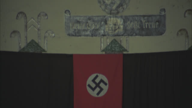 PULL BACK FROM NAZI INSIGNIA ON WALL. SIGN SAYS SALA ROZPRAW SS. NAZI LECTURE FLAG, SWASTIKA. NEG CUT.