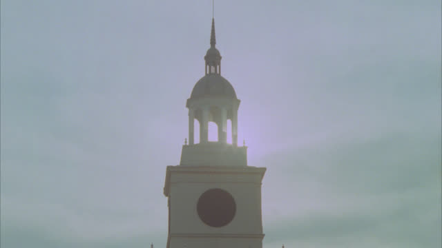 pull back from steeple and cross on top cupola to show two story brick church or catholic school with cars parked in parking lot and nuns and children walking in fg. - steeple stock videos & royalty-free footage