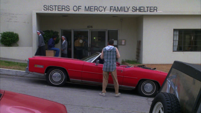 """wide angle of the """" sisters of mercy family shelter """" homeless mission from across the street / nun or sister talking to a boy in front of the shelter / red convertible drives up r-l and parks in front / two people in the car get out / two takes / in seco - family convertible stock videos & royalty-free footage"""