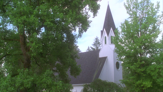 wide angle of white wooden church nestled among green trees with steeple   camera pans down principals in the cemetery in the fg at a funeral / could be country or rural area for small wedding chapel - cemetery stock videos & royalty-free footage