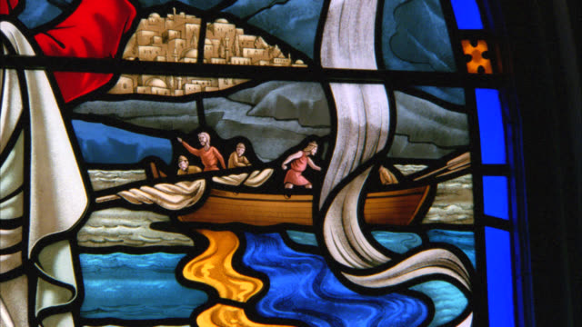 CLOSE ANGLE OF STAINED GLASS WINDOWS DEPICTING RELIGIOUS SCENE OF JESUS WITH HIS ARMS OUTSTRETCHED OVER RIVER WITH DEPICTION OF JERUSALEM IN THE BG. NEG CUT. CHURCHES. CATHEDRALS.