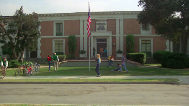 "WIDE ANGLE OF TWO STORY BRICK BUILDING, HIGH SCHOOL WITH ""MUMFORD HIGH SCHOOL"" SIGN ABOVE ENTRANCE. STUDENTS, TEENAGERS IN FRONT OF BUILDING, ENTER AND EXIST, WALKING AROUND AND NEAR BIKE RACKS. AMERICAN FLAG ON FLAGPOLE IN FRONT."