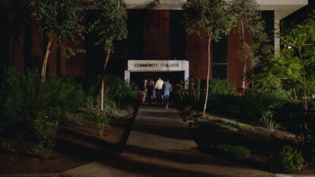 """wide angle of people, college students, walking down walk way toward entrance to building with sign above door that reads """"community college"""" - community college stock videos & royalty-free footage"""