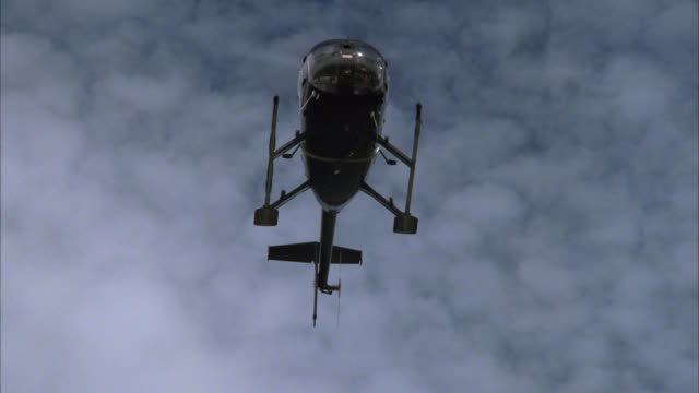 up angle to underside of helicopter as it is hovering. against blue sky with clouds. could be used for helicopter landings. - hovering stock videos & royalty-free footage