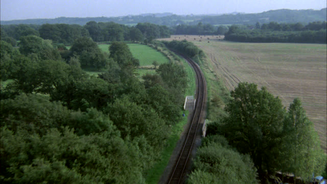 aerial along railroad tracks thru english countryside. might work for farmland, countryside or rural area. - rail transportation stock videos & royalty-free footage