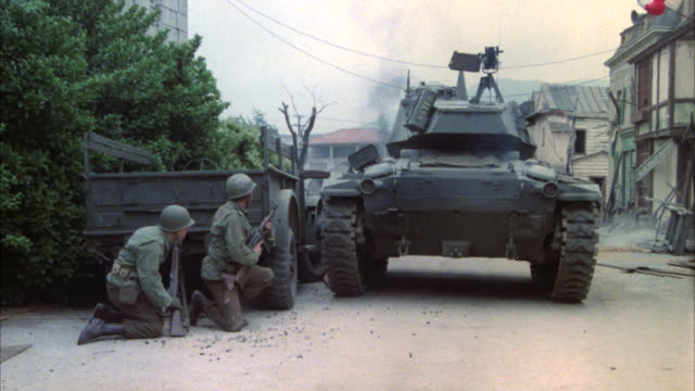 WIDE ANGLE OF TANK IN DESTROYED CITY, TOWN, OR VILLAGE. TWO MILITARY, ARMY SOLDIERS (PRINCIPALS?) IN FG DUCKING IN COVER BEHIND TRUCK.  ONE SOLDIER BEGINS TO FIRE HIS MACHINE GUN AT OTHER SOLDIERS IN BG ACTION. BATTLE.