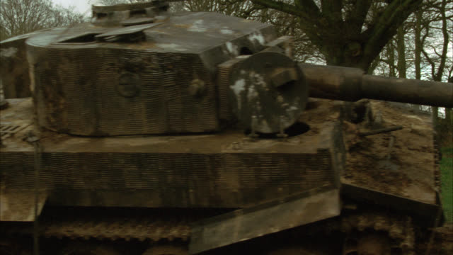 PAN LEFT TO RIGHT FROM SMOKING, BLOWN-APART TANK ON BATTLEFIELD, TO SECOND TANK WITH THREE SOLDIERS ABOARD DRIVING ON DIRT COUNTRY OR RURAL ROAD. OVERCAST AND CLOUDY. MILITARY OR ARMY. MILITARY VEHICLES.