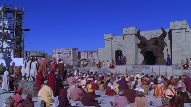 wide angle of crowd sitting outside pagan temple with giant bull head covering entrance. stone building. men in purple robes stand on platform in bg. could be priests. scaffolds in bg. people in crowd wear turbans, togas, and robes. could be biblical city - religiöse darstellung stock-videos und b-roll-filmmaterial