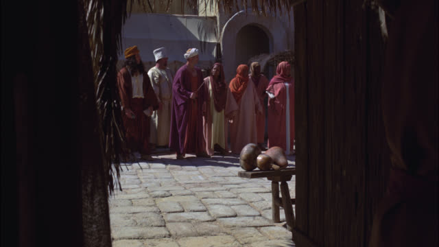 medium angle of marketplace or town square through pov of vendor or shop doorway. people or crowds in robes standing near cobblestone street. could be ancient rome. biblical times. - religiöse darstellung stock-videos und b-roll-filmmaterial