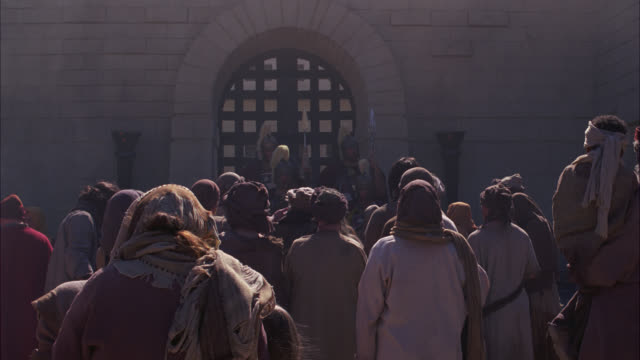 medium angle of crowd or mob of townspeople at iron castle gate trying to get in. ancient roman guards or soldiers fight them back. biblical times. - soldat stock-videos und b-roll-filmmaterial