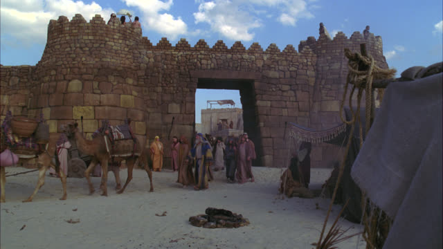 vídeos de stock, filmes e b-roll de wide angle of townsfolk, villagers or crowd of people waving goodbye. walking out through door or entrance in stone wall. could be castle or city wall. farm animals, donkeys and camels. desert. could be ancient middle east. - aldeia