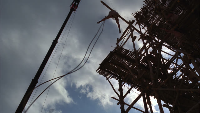 up angle of construction workers or laborers on wooden scaffolding surrounding ancient building. one man on a cart rolls off the ledge. he grabs onto a rope and cart falls down. sky. stunt. 40 fps. - scaffolding stock videos & royalty-free footage