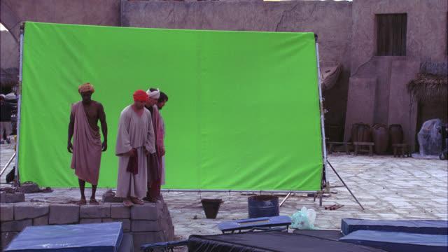 vídeos y material grabado en eventos de stock de wide angle of men jumping off of stone wall. green screen. stunt. - moving image