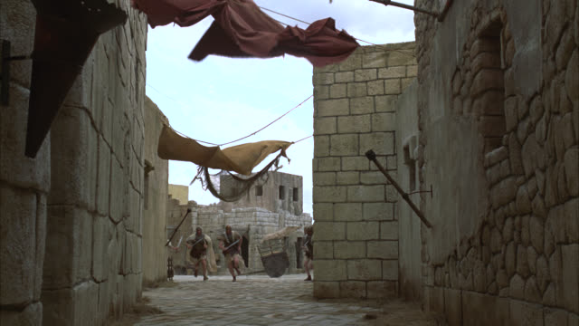 pan right to left from deserted alley in ancient city. could be rome. stone walkways and walls. clothes or pieces of cloth hanging from lines over alley. soldiers in helmets carrying swords run through alley. windy. - rom stock-videos und b-roll-filmmaterial