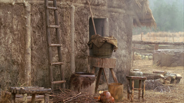 vídeos de stock, filmes e b-roll de medium angle of lower class rural village. could be medieval times. straw and mud house. wood furniture and tools outside. straw and dry fields in bg. wooden ladder leans against house. - medieval
