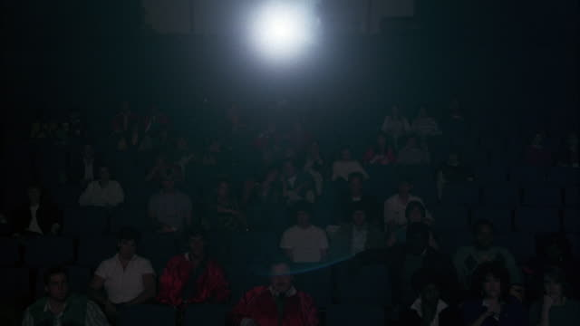 medium angle of stadium seating seats in auditorium or movie theatre. audience faces pov as projector or spotlight flashes on top toward pov. - auditorium stock videos & royalty-free footage