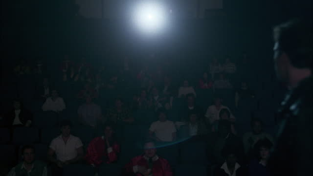 wide angle of theater with  stadium seating seats in auditorium or movie theater. audience faces camera, and spotlight or projector light beams at the camera. - zuschauerraum stock-videos und b-roll-filmmaterial
