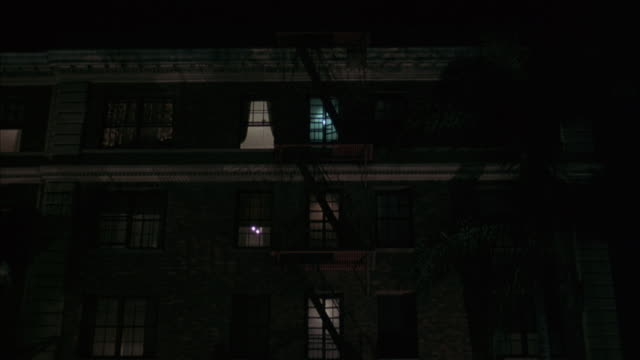 medium angle establish of older brick or stone multi-story apartment building. see lights on in windows. see fire escape. see silhouetted figure appear in top window as clip ends. - fire escape stock videos & royalty-free footage