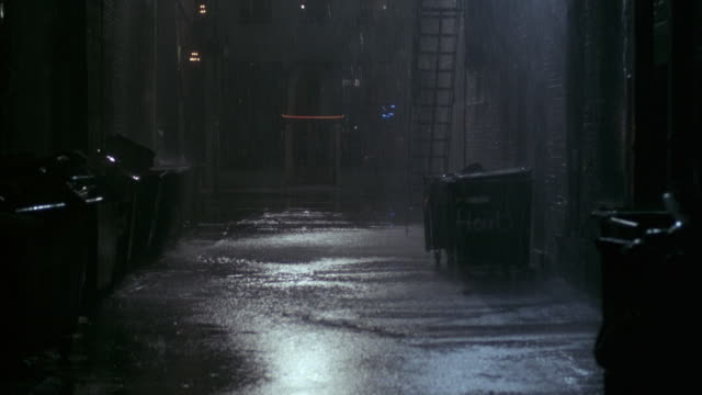 medium angle of heavy rain falling in alley. see trash dumpsters. see fire escape and brick walls. see water accumulating on ground. see pedestrians with umbrellas walk by on sidewalk. see cars travel on street by opening of alley in background. - gasse stock-videos und b-roll-filmmaterial