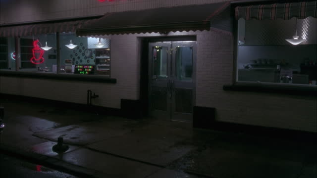 MEDIUM ANGLE ESTABLISH OF WHITE BRICK BUILDING COFFEE SHOP. SEE COFFEE SHOP LIGHTS ON AND EMPTY COUNTERS.