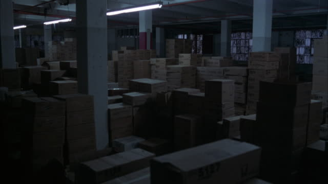 vídeos y material grabado en eventos de stock de medium angle establish of office storage room. see fluorescent tube lighting. see stacks of boxes filling most of room. see square support columns. see windows in background. could be government building storeroom. - cuarto almacén