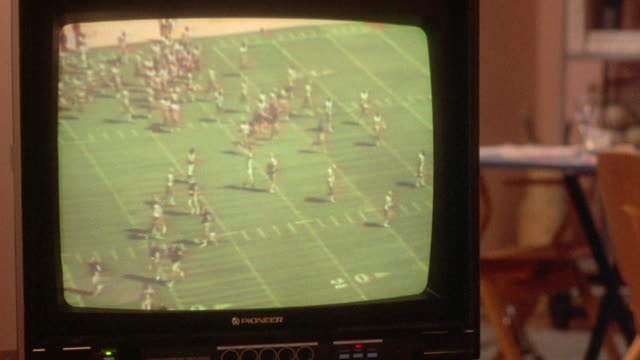 "medium angle of ""pioneer"" television showing football game. football players with ""w"" and ""n"" labeled helmets on football field. - 1986 stock-videos und b-roll-filmmaterial"
