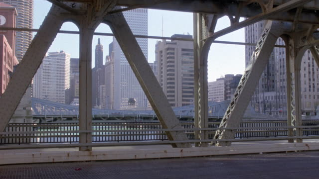 medium angle of drawbridge in foreground, skyscrapers in background, see another bridge in front of skyscrapers. see metal structures of bridge and railing in front of sidewalk. road in foreground. - drawbridge stock videos and b-roll footage