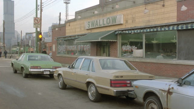 "MEDIUM ANGLE OF DINER ON SIDE STREET CORNER. DINER IS ONE STORY BRICK BUILDING, WITH SIGN READING ""SWALLOW"" IN CENTER."