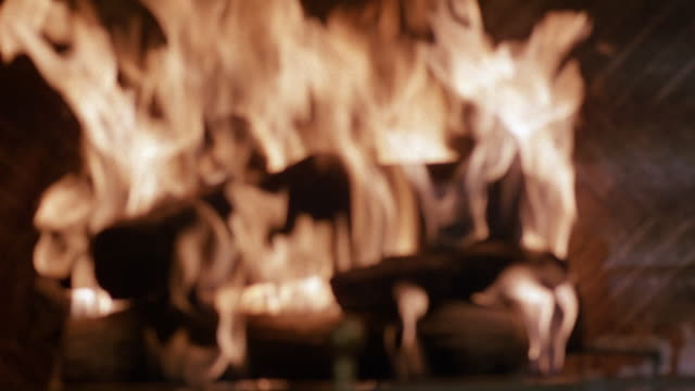 medium angle insert of roaring fire in fireplace going from out-of-focus to in-focus. see return to out-of-focus. see imitation logs and brass screen at bottom of fireplace. see bricks at side of fireplace. - brass stock videos & royalty-free footage